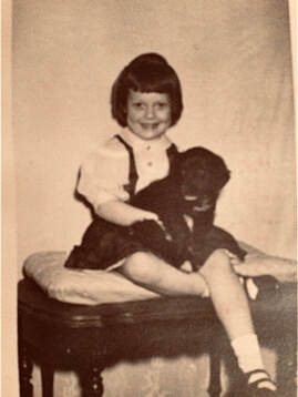 Photo of toddler Susie Caron with her little Black Dog